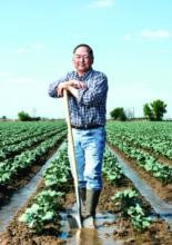 bob-sakata-leaning-on-shovel-in-field-cfvga